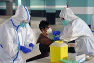 Dos sanitarios someten a la toma de muestras para una prueba PCR durante un cribado en Portugalete.