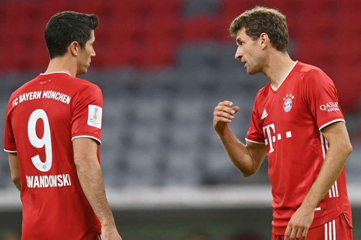 Müller habla con Lewandowski durante un partido.
