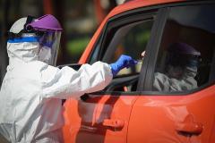 Un sanitario toma muestras a un conductor para una prueba de coronavirus en el hospital miltar de Sevilla.
