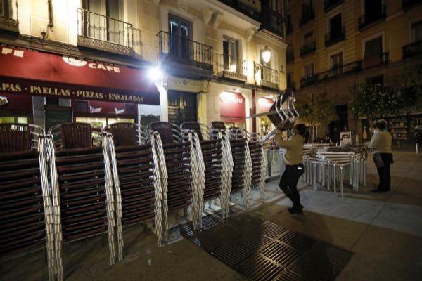 Uno de los restaurantes de la plaza de la Cruz Verde en Madrid comienza a recoger sus mesas antes de las 22:00 horas, por el cierre de la capital.