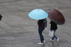 Escolares se protegen de la lluvia con paraguas este viernes en Bilbao.