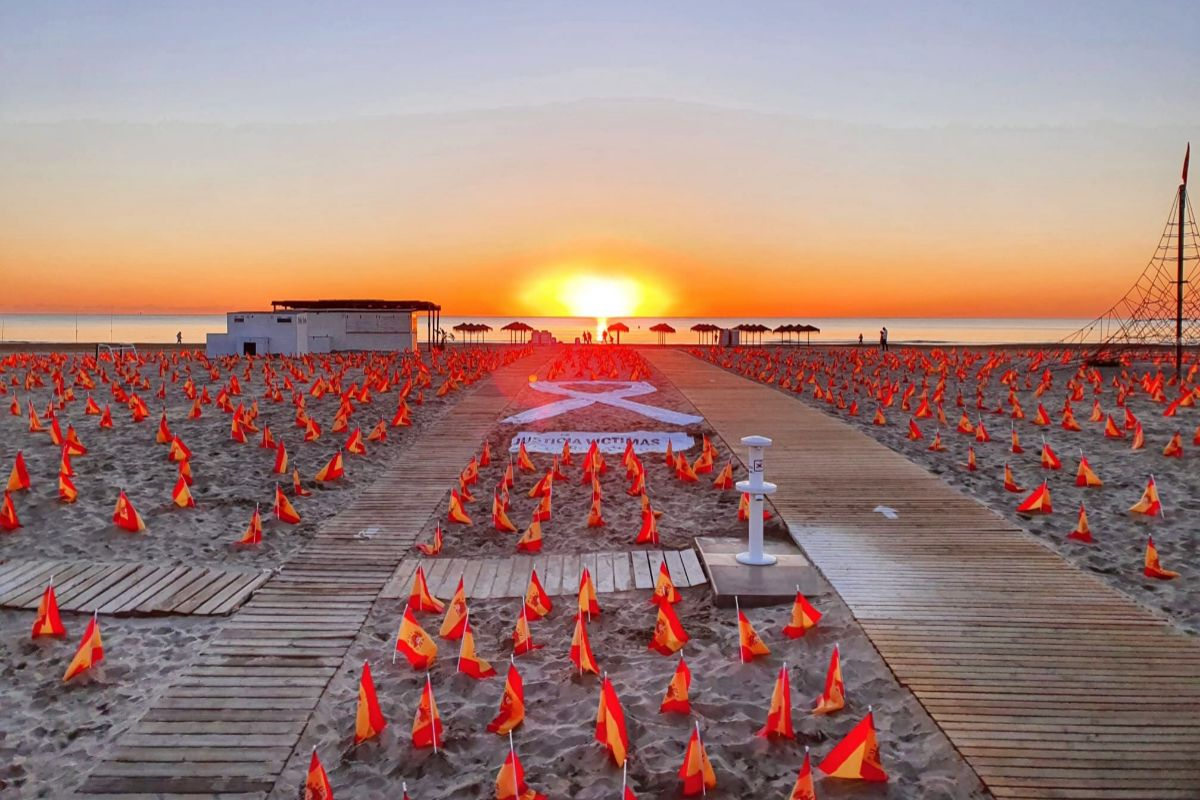 Amanecer en la playa de la Patacona, llena de banderas.