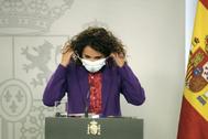 La ministra de Hacienda, María Jesús Montero, quitándose la mascarilla antes de una rueda de prensa.