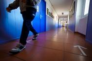 Un alumno pasea por el pasillo de un colegio.