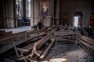 Un hombre revisa los escombros en el interior de la catedral de Shusha.