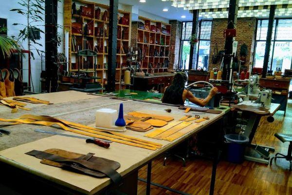 Una trabajadora cose un producto de piel en el Taller Puntera, uno de los pequeños comercios de Madrid apuntado a la iniciativa 'Más que un local'