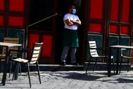 Un camarero con mascarilla, en una terraza vacía en Madrid