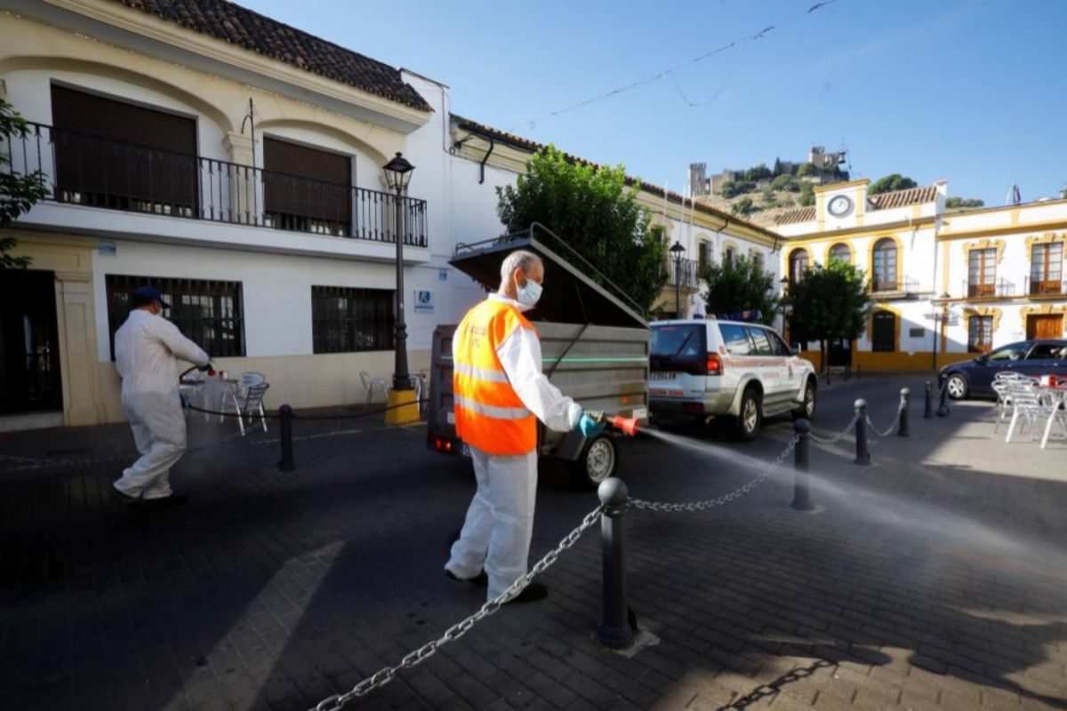 Operarios municipales desinfectan las calles de la localidad cordobesa de Almodóvar del Río después de decretarse su confinamiento temporal.