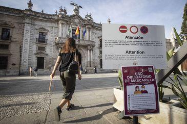 Entrada principal al Rectorado de la Universidad de Sevilla, con un cartel donde se avisa de medidas extraordinarias por el Covid.