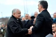 Kaczynski, presidente del Pis polaco (izqda.) estrecha la mano de Orban.