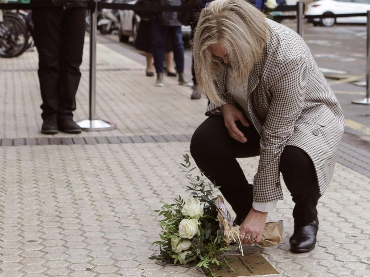 La hermana de Begoña Urroz coloca flores sobre la placa que la recordará en San Sebastián.