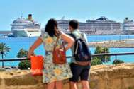 Una pareja de turistas observa dos cruceros en la bahía de Palma antes de la pandemia.