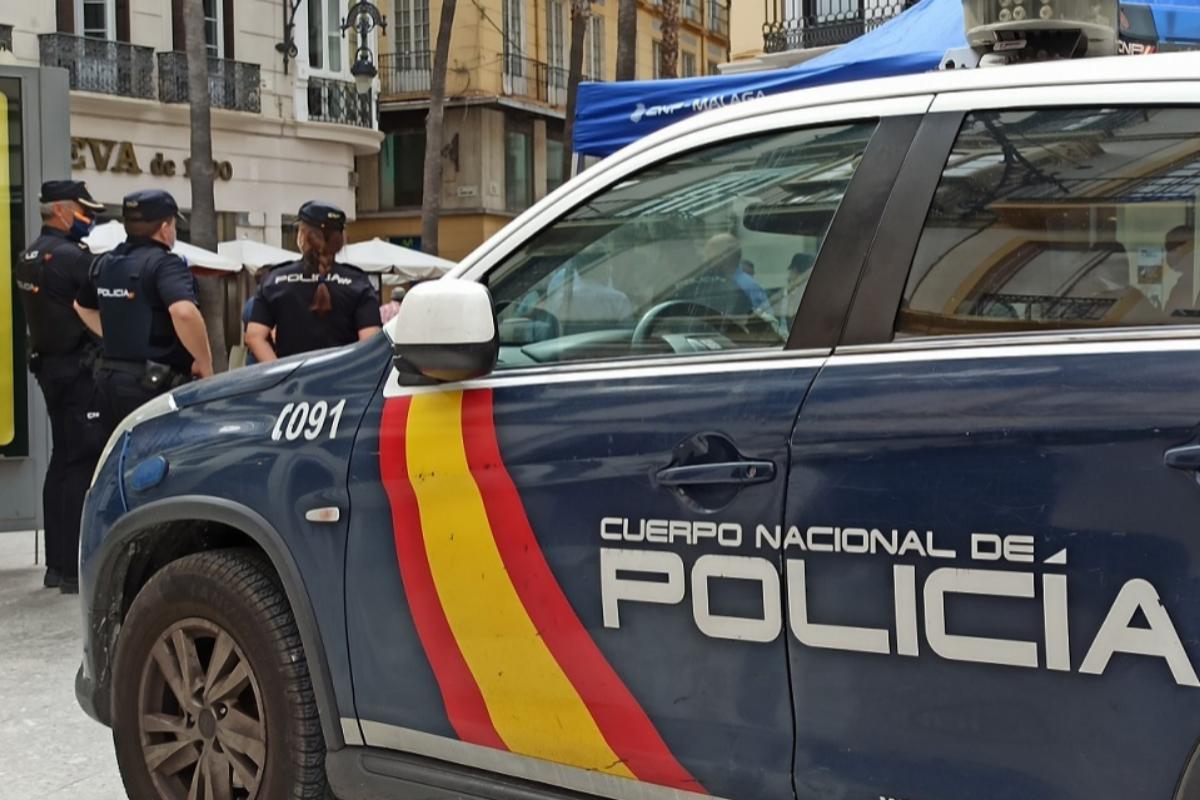 Unos agentes, tras un vehículo policial.