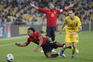 Adama cae al suelo ante un rival, con Ramos detrás.