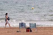 Una mujer pasea por la playa en Valencia.