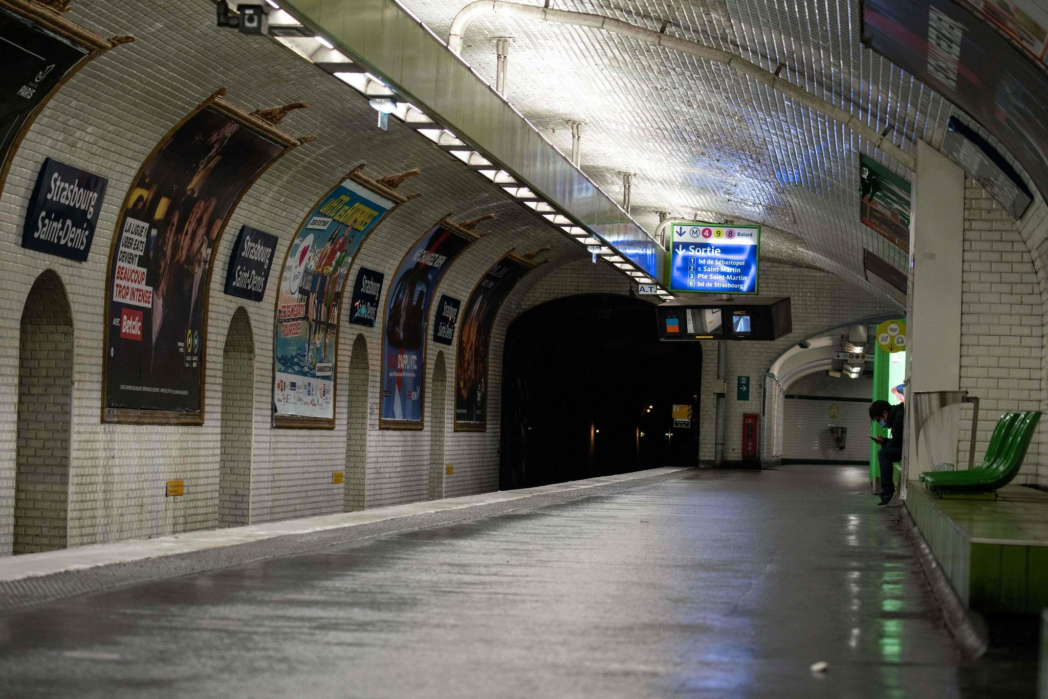 Un hombre espera el metro en una solitaria estación.