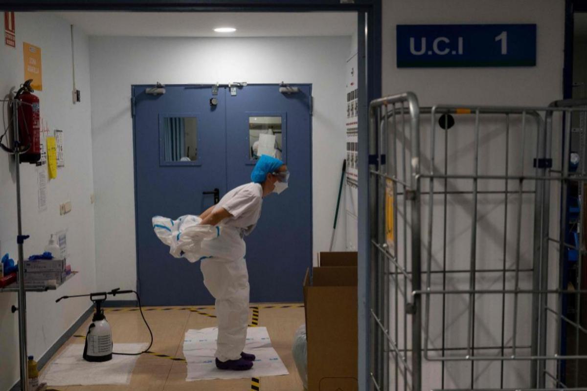 Una sanitaria se quita el traje protector tras salir de la UCI en el Hospital Severo Ochoa de Madrid.