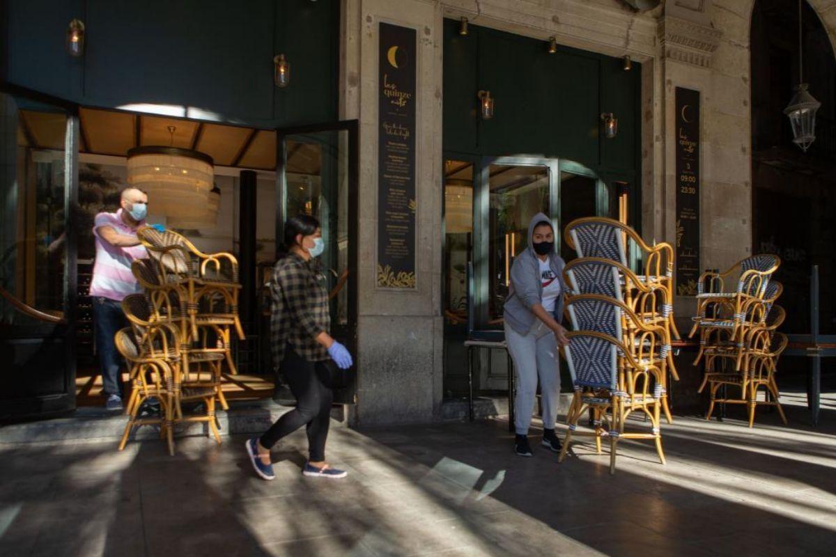 Camareros recogen la terraza de un bar