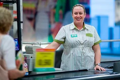 Una cajera atiende a una clienta en la cola del supermercado.