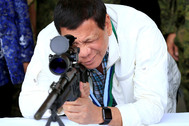 El presidente de Filipinas, Rodrigo Duterte, revisa un rifle de francotirador en la Base Aérea de Clark, en junio de 2017.