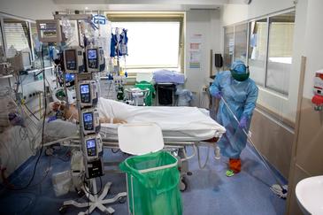 La limpiadora Lina desinfecta la habitación de un paciente de Covid en la UCI.