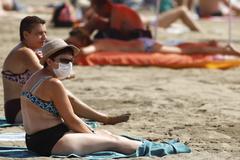 Una mujer, con mascarilla, en una playa canaria en agosto.