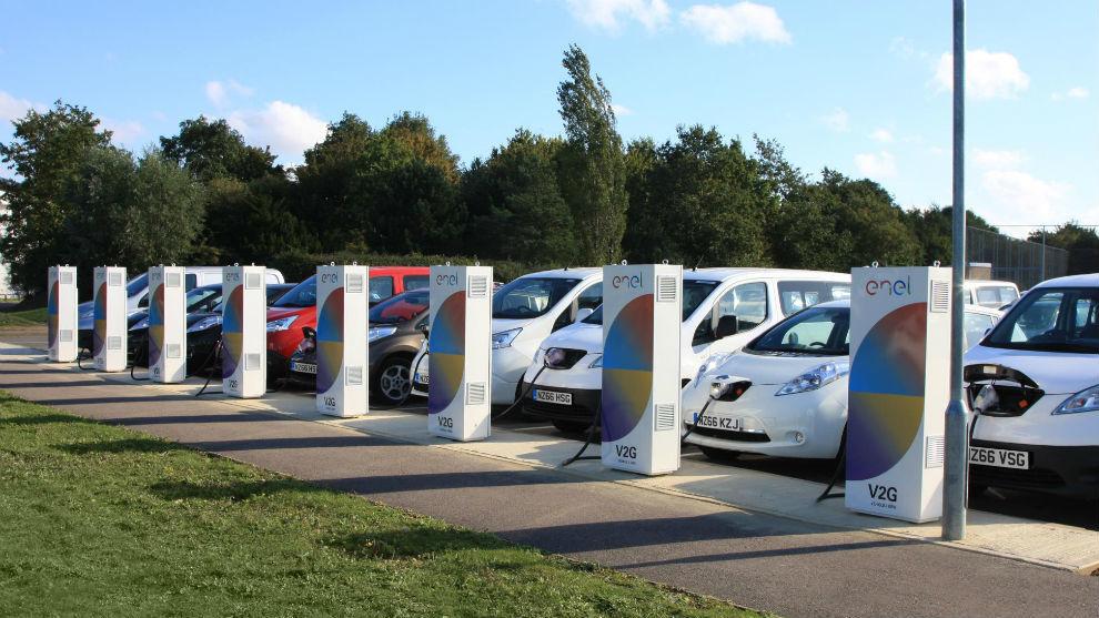 Varios coches eléctricos enganchados a puntos de recarga.