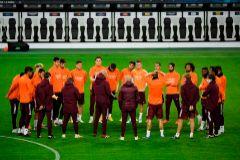 Zidane habla con sus jugadores sobre el césped del Borussia Park.