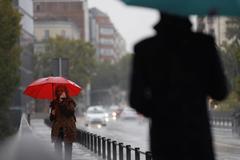 Dos transeúntes caminan entre la lluvia por las calles de Madrid.