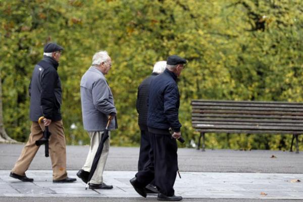 Pensionistas y jubilados paseando por un parque en Bilbao.