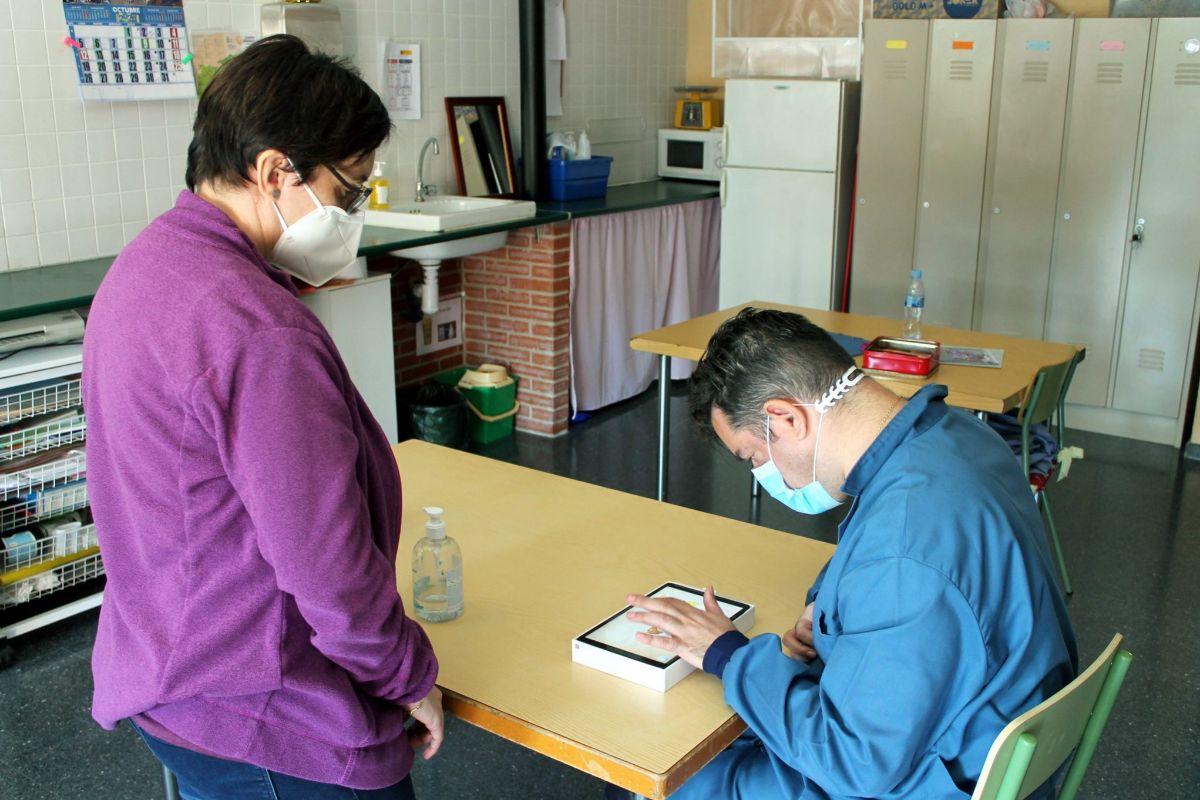 Una monitora supervisa a un usuario que está haciendo uso didáctico de una tablet