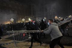 Un grupo de manifestantes trata de lanzar las barreras de seguridad a los mossos en Barcelona.