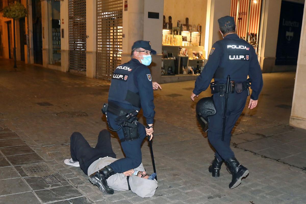 Agentes de la Policía Nacional detienen a un joven tras intentar meter fuego a una barricada en la calle Mesones de Granada.