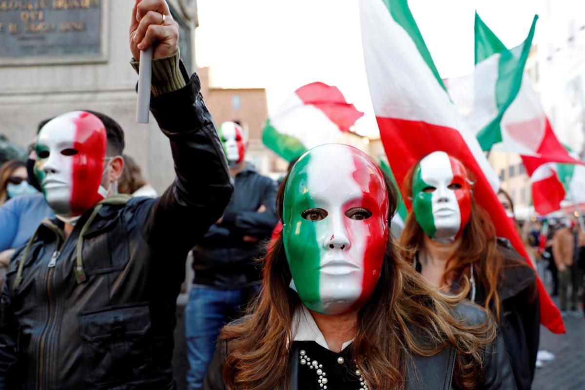 Personas con máscaras de la bandera italiana protestan en Roma contra las medidas.