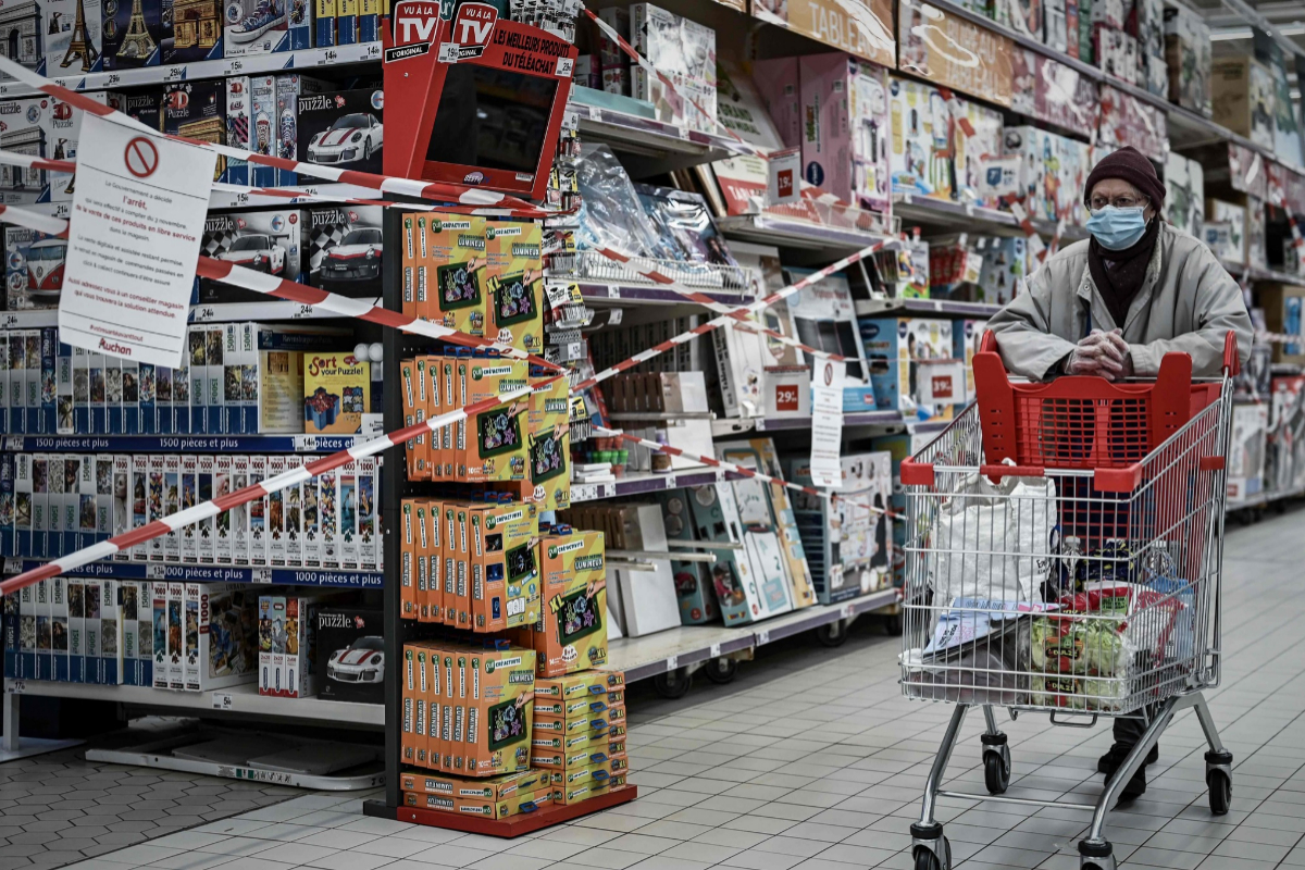 Una mujer camina junto a la cerrada sección de juguetería de un supermercado en Burdeos.