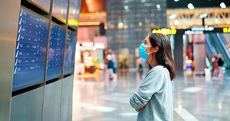 Viajera con mascarilla en un aeropuerto internacional.