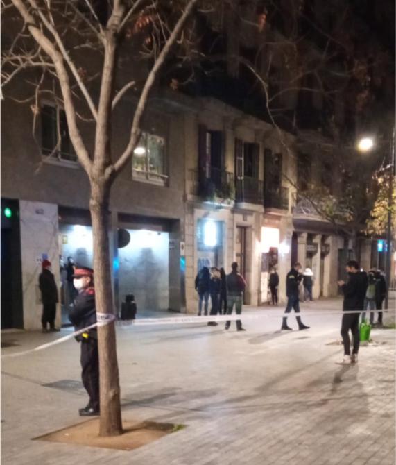 La zona donde han tenido lugar los hechos, acordonada, mientras agentes de la Guardia Urbana buscan casquillos.