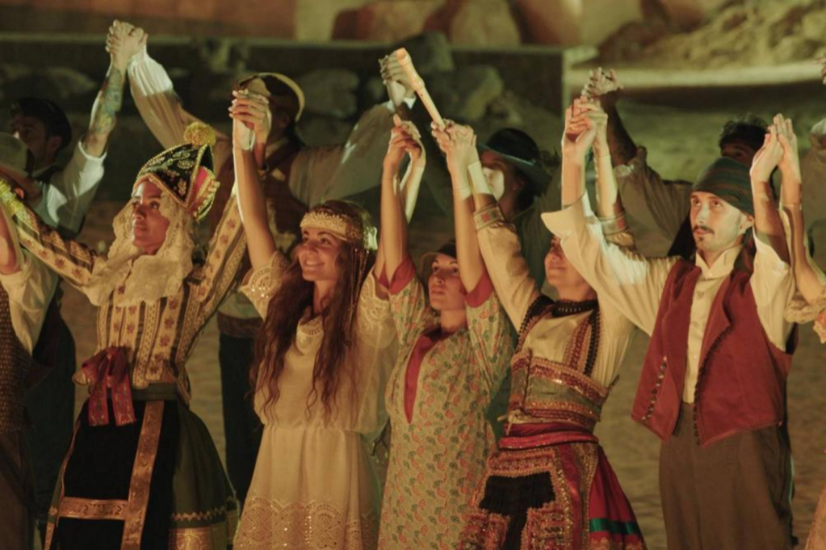 Actores y bailarines participantes en la representación saludan al público.