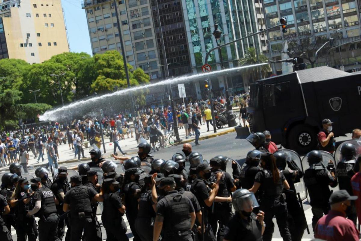 Un vehículo polcial lanza agua contra los seguidores de Diego Armando Maradona durante los incidentes en los accesos al velatorio del futbolista | Matías Baglietto / AFP