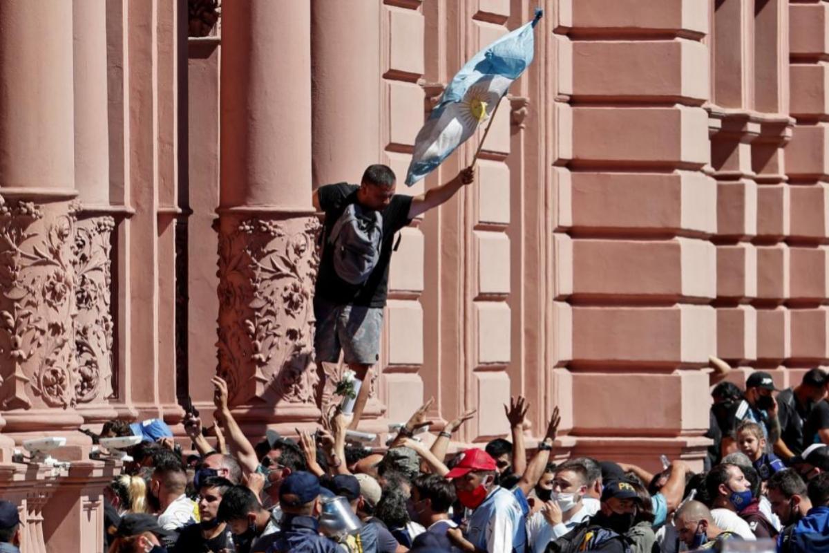 Un aficionado se encarama por la fachada de la Casa Rosada, donde se había instalado el velatorio de Maradona | Alejandro Pagni / AFP