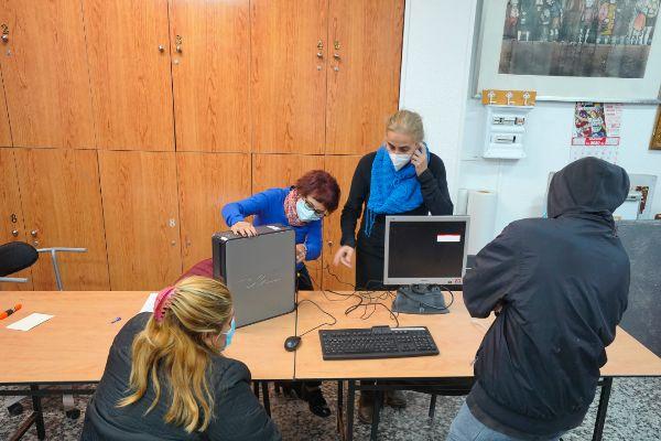 Trabajadoras de la Asociación Vecinal de Aluche entregan un ordenador a una de las 230 familias que lo necesitan