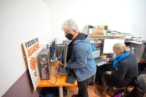 Unas trabajadoras de la Asociación de Vecinos de Aluche preparan los equipos que han de entregar a las familias
