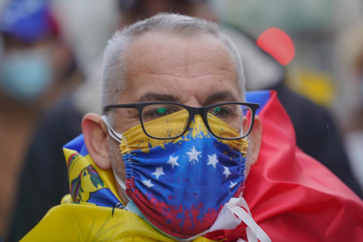 Un manifestante usa una mascarilla con la bandera venezolana.