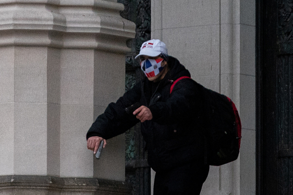 A man wearing a protective mask points his guns outside the Cathedral Church of lt;HIT gt;St lt;/HIT gt;. lt;HIT gt;John lt;/HIT gt; the Divine in Manhattan