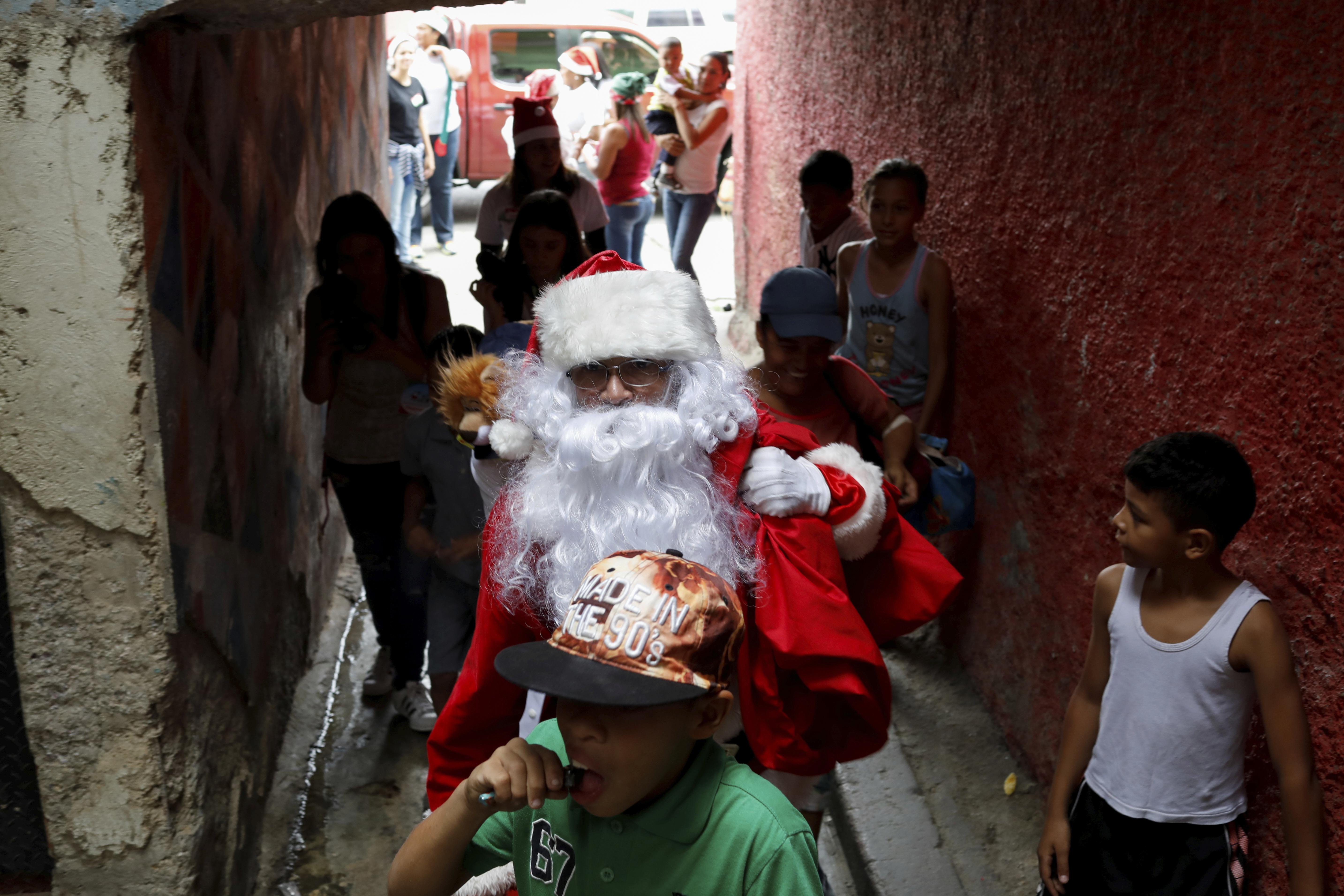 Richard Gamboa, disfrazado de Santa Claus, reparte comida.