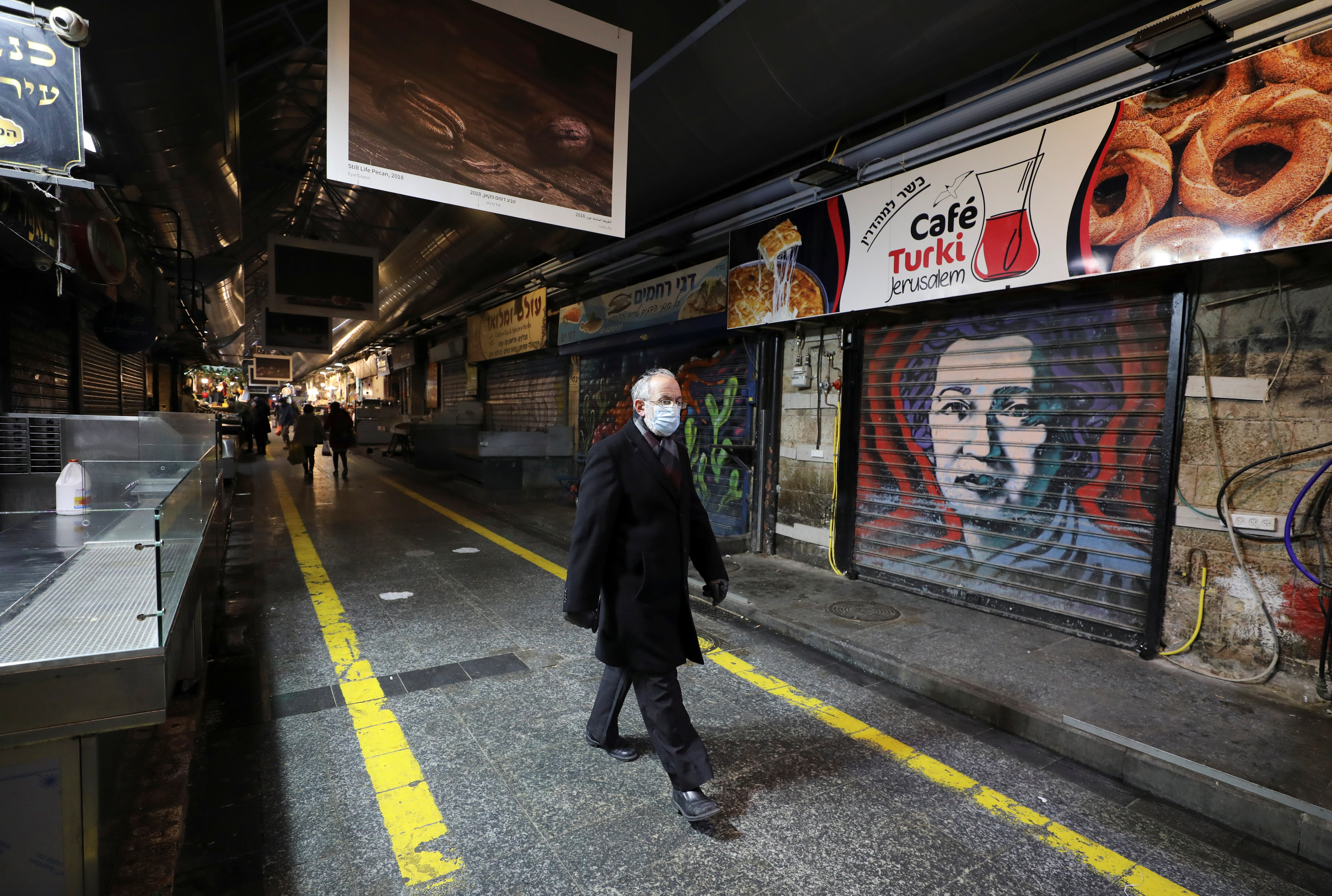 Un hombre pasea junto a tiendas cerradas, en Jerusalén.