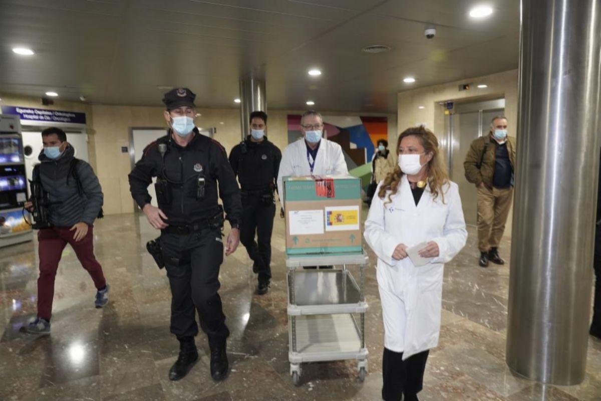La consejera Sagardui junto a un sanitario y un ertzaina traslada la primera remesa de vacunas contra el Covid-19 que llegaron a Euskadi el domingo 27 de diciembre.