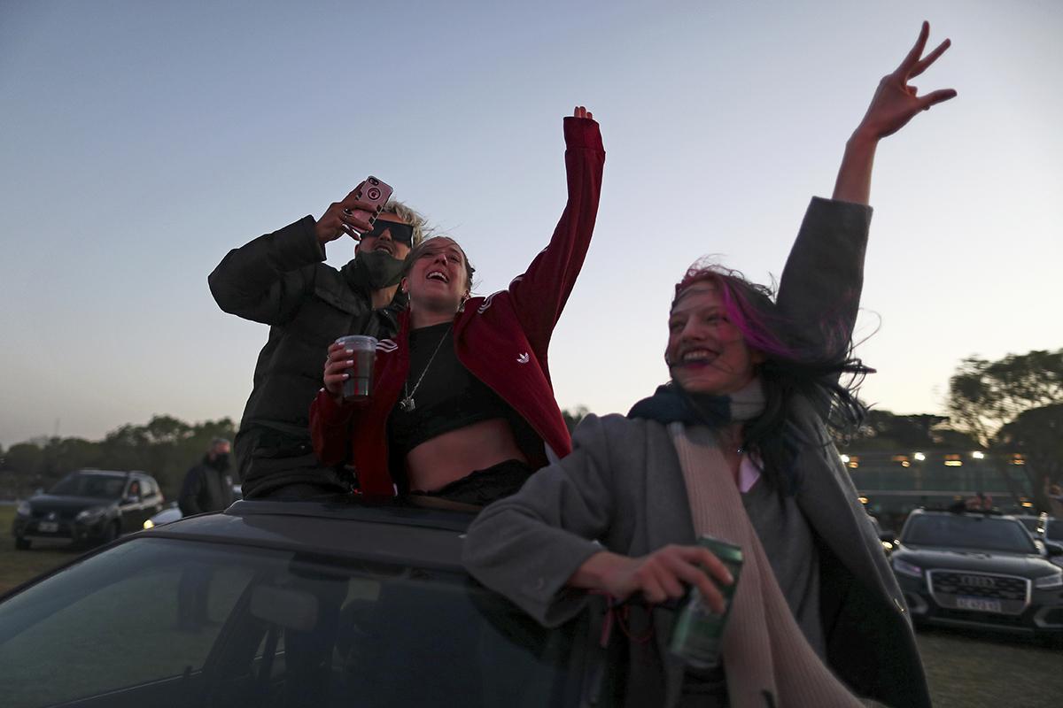 Jóvenes asisten en sus coches a un concierto en Buenos Aires.