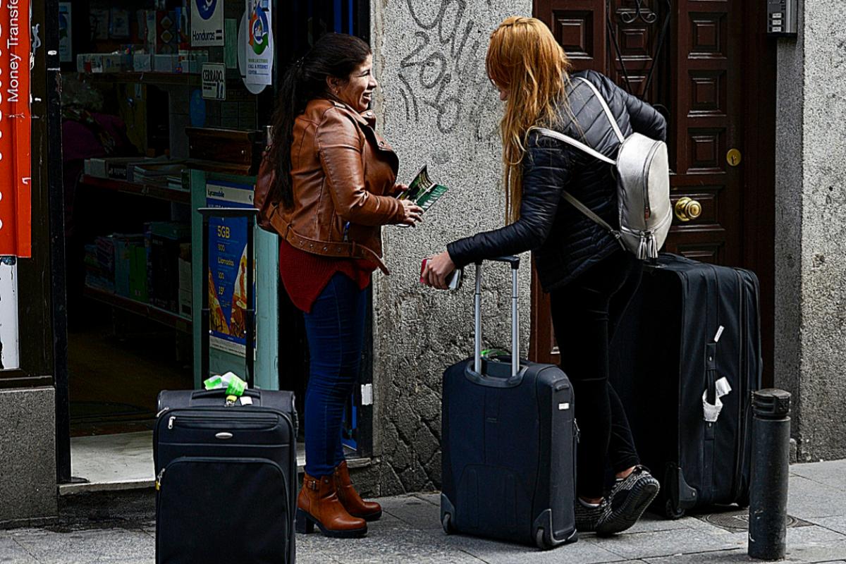 Dos turistas esperan con sus maletas ante un bloque de pisos en Madrid.