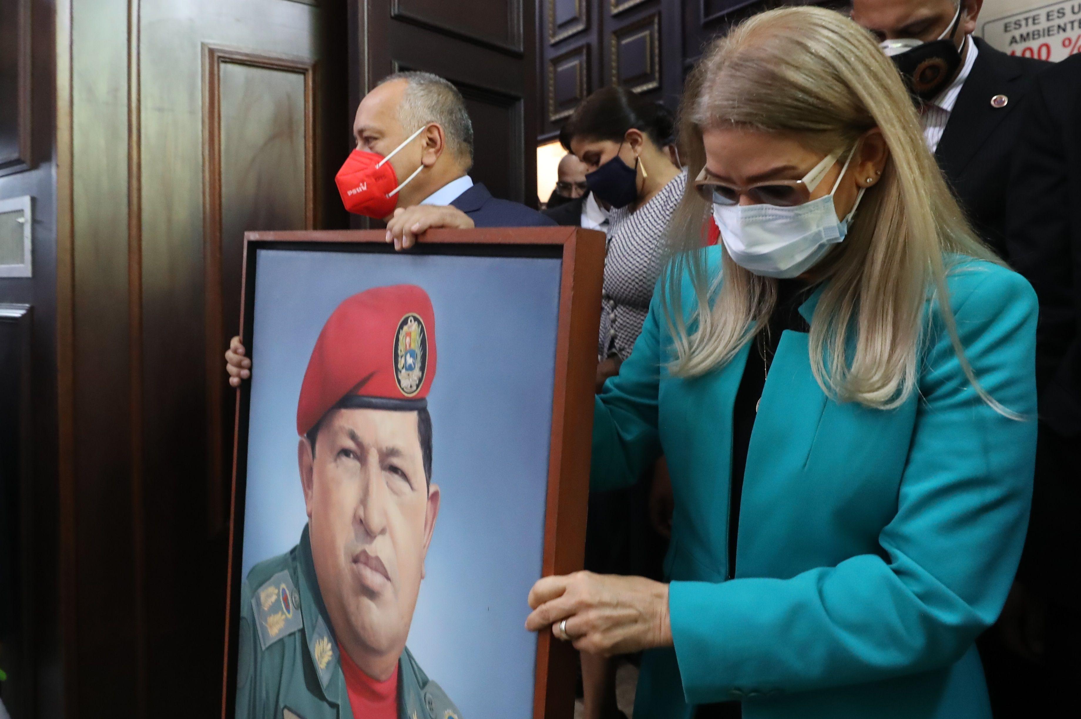Cilia Flores (d) y Diosdado Cabello (i) portan una imagen de Hugo Chávez en su entrada a la Asamblea Nacional.